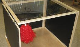 Image of a large foldable sensory exploration frame with red object.