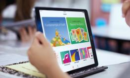Student using an iPad displaying Swift Playgrounds graphics.