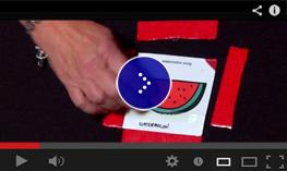 Ellen puts a sticker on a color highlighting board in black with red square.