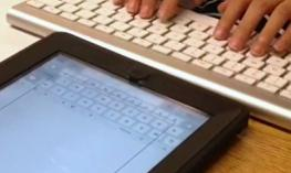A student is typing on a keyboard that is displaying on the iPad.