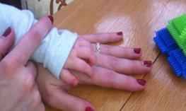 Photo of a toddler hand that is being touched by a finger.