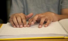 A student uses his hand to read braille.