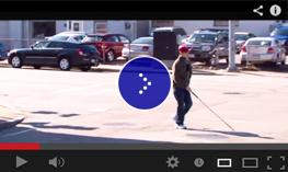 A visually impaired boy navigates across a street intersection with his cane.
