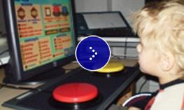 A young boy is looking at a computer screen with a big red button.