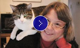 A woman sits with her cat on her shoulder.