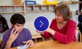 A student sits at the desk with his teacher.