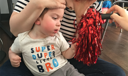 cvi child looks at red shiny pom pom