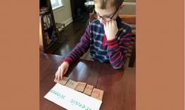 a student studies the syllables of a long phrase