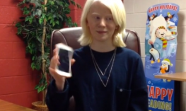 Girl with albinism holding iPhone