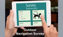 """Photo of a finger pointing to a digital survey with a guide dog image and text, """"Outdoor Navigation survey."""""""