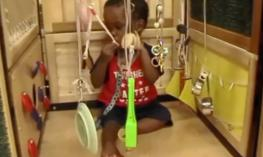 A child in a Little Room explores a toothbrush