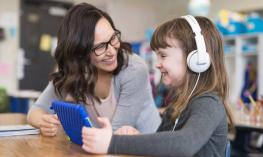 Photo of a smiling girl with headphones holding an iPad with a happy teacher beside her.