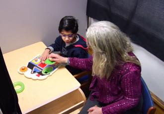 Dr. Lueck showing a young boy how to play a tactile game.