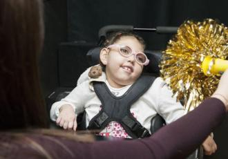 Photo of a young girl wearing glasses and looking at a shiny yellow pom pom.