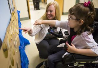A young girl in a wheelchair pointing to a mural along with her teacher.