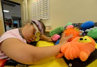 girl with brightly colored stuffed animals on a tray