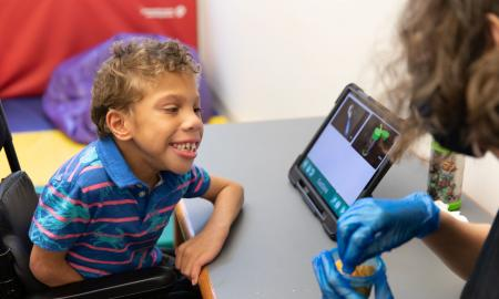 A smiling student turns from his tablet device, where picture symbols are displayed