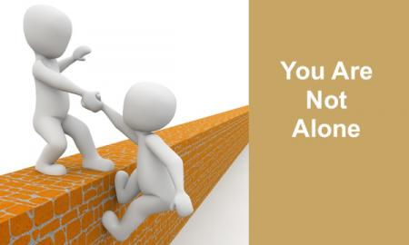 "2 Cartoon people: One person pulling second person up and over the wall with text, ""You are not alone"""
