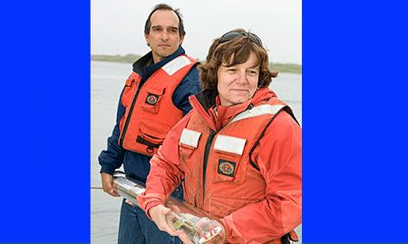 Amy Bower & colleague wearing life jackets, standing on a ship holding a research float (long glass tube filled with electronics