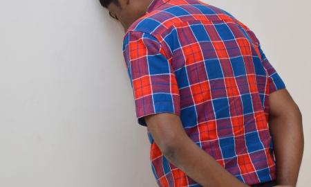 Student hiding his face in the wall with his hands behind his back.