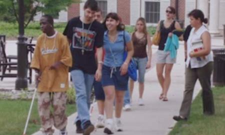 A young man walks with his cane among other students on college campus.