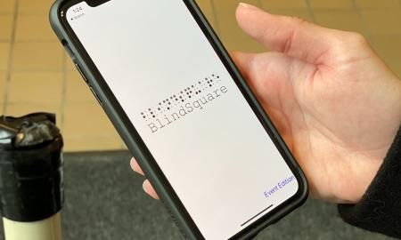 Image of someone holding a white cane and an iPhone with the BlindSquare Event app visible on the screen