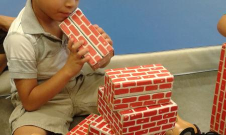 A yound boy sits on the floor with building brick blocks.