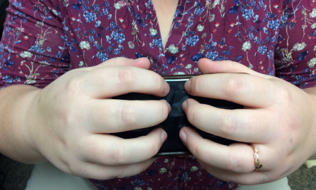 Hands holding an iPhone with the screen facing out; thumbs & pinky holding the sides. Other fingers of both hands on screen