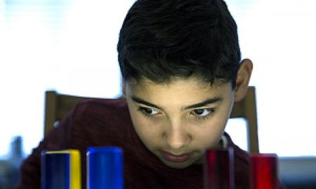 A student gazes at colored cylinders on a lightbox