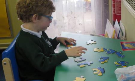 A student works a jigsaw puzzle of large two-tone pieces