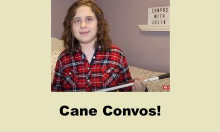 Julia, a teen with curly shoulder-length hair sitting on her bed holding her cane.