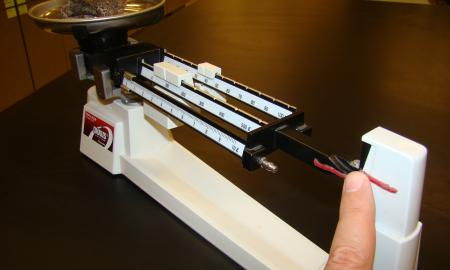 This image shows the adapted triple beam balance in use.