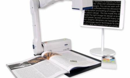 Photo of an E-Bot pro focused on an open book with text displayed on an iPad which is on a stand.