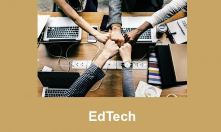 "Photo of 5 people fist bump over a table holding open computers and smart phones with text, ""EdTech""."