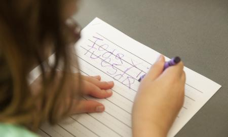 A girl is using a crayon to write some words on a paper.