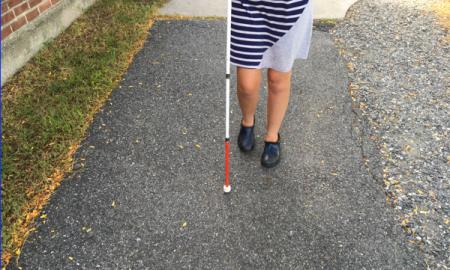 Photo of a student's feet and cane traveling on a school sidewalk.