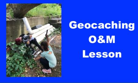 "Two kids reaching behind pipes searching for geocached treasure and text, ""Geocaching O&M Lesson""."