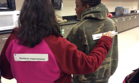 One student reads the scientific method step from the back of a second student.