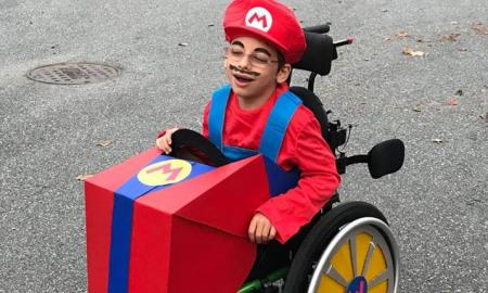 A boy dressed as Super Mario in a wheelchair