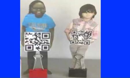 "Two QR Kids standing upright on a desk: Cutout photo of each student with hands ""holding"" a QR code square. Binder clip at feet."