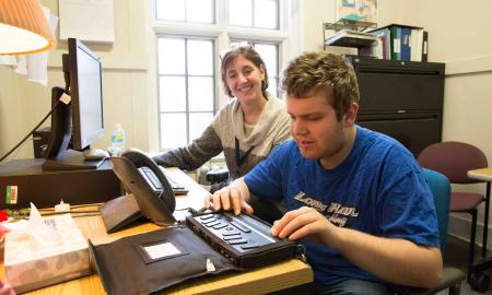 A counselor sits with a student using a refreshable braille display