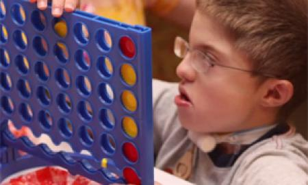 A boy with glasses holding a board game.