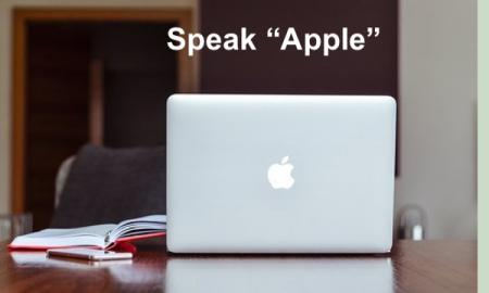 "Desktop with Apple Computer, iPhone and open manual with text, ""Speak Apple"""