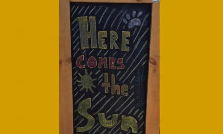 Photo of a chalkboard with a sun, paw print & the words Here Comes the Sun written in different colored chalk.