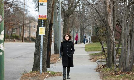 Woman using white cane to walk to bus stop