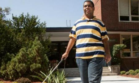 Student walking with cane on college campus