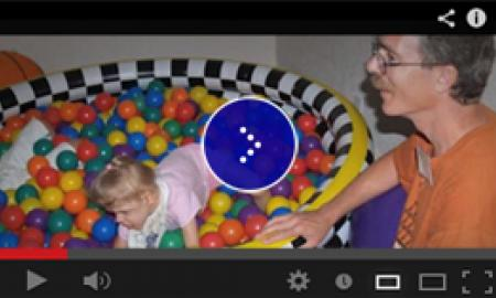 A young girl with glasses in a pool of colorful plastic balls.