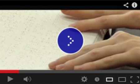 A close up of both hands tracking the lines of braille type.