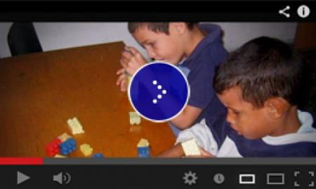 Two blind young boys sitting at a table in a classroom in Cuba and playing with lego pieces.