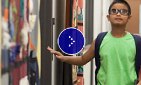 A visually impaired boy is navigating the hall.